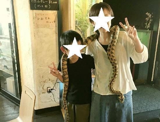 爬虫類カフェ「爬虫れぼ」で首にヘビを巻いた親子